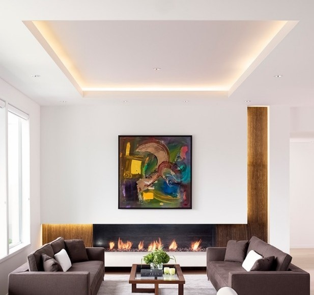 Living room with a fireplace and an indirectly lit ceiling