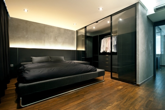 black bedroom with a walk-in closet with glass doors