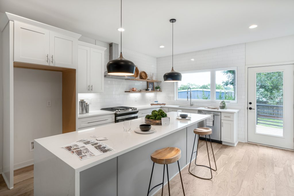 White kitchen with recessed and pendant lighting