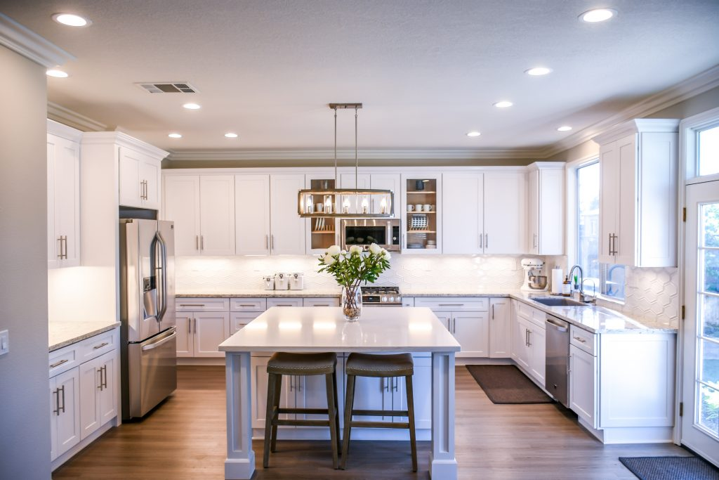 White kitchen lit with recessed spotlights