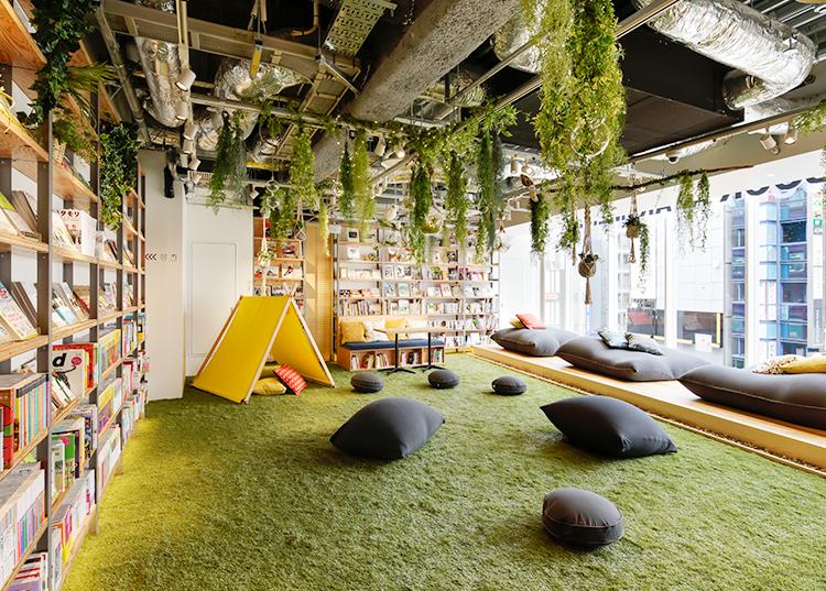 Espace de repos d'un bureau avec plantes suspendus et des coussins
