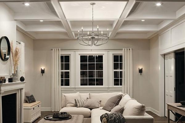Salon éclairé avec un luminaire suspendu et des spots encastrés LED.